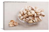 pistachio nuts in shell lying on glass plate , Canvas Print