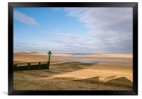 Green groyne marker and sunlit beach under a heavy, Framed Print