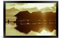 Sun rising over cute little wooden huts perched on, Framed Print